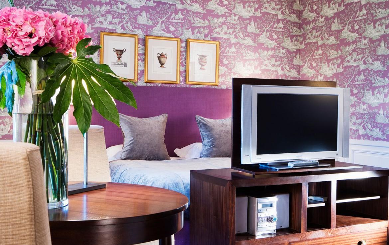 Golf-reizen-frankrijk-regio-parijs-Chateau-de-Villiers-le-Mahieu-slaapkamer-paars-ingericht-tv-en-tafel-golf-expedition
