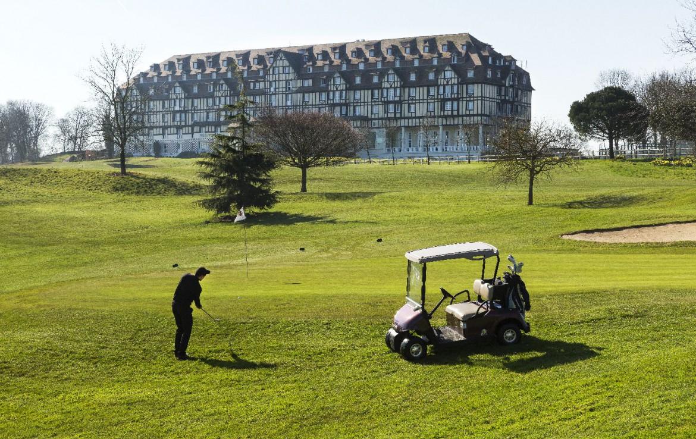 golf-expedition-golf-reizen-frankrijk-regio-normandië-hotel-du-golf-barriere-golfer-op-golfbaan-met-hotel-op-achtergrond.jpg