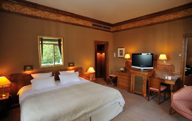 golf-expedition-golf-reizen-frankrijk-regio-rhone-alpes-domaine-de-divonne-bruin-ingerichte-slaapkamer-met-tv.jpg